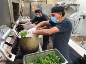 Cooks prepare a meal in the kitchen of Nexus Brewery in Albuquerque